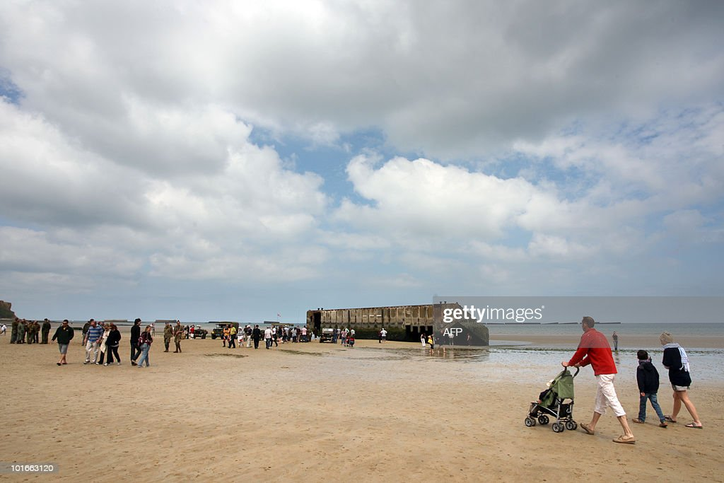 People walk on June 6, 2010 on Arromanches-les-Bains beach, western France, on the day celebrating the 66th D-Day anniversary on June 6, 1944 allied landings in Normandy, then occupied by Nazi Germany. AFP PHOTO KENZO