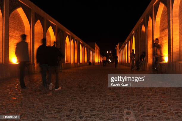 People walk on Khaju Bridge at night. Khaju Bridge is arguably the finest bridge in the province of Isfahan, Iran. It was built by the Persian...