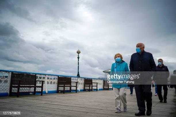People walk on Llandudno Pier before new Covid-19 regulations come into effect on September 30, 2020 in Llandudno, United Kingdom. New local lockdown...
