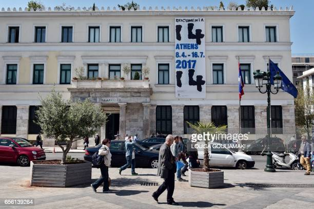 People walk on March 21 2017 past the Athens municipality building and a banner advertising the prestigious contemporary art festival 'Documenta' to...