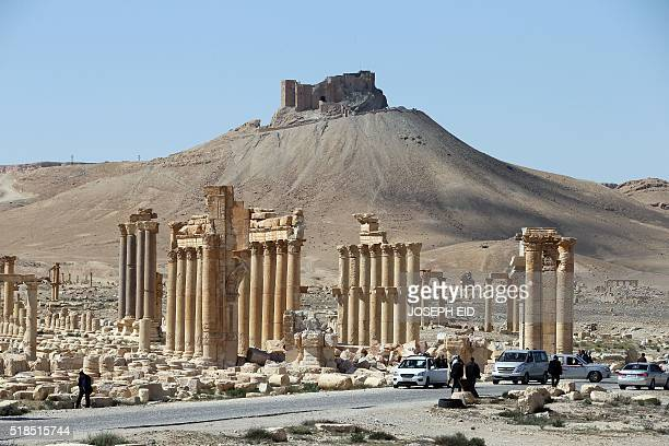 People walk on March 31, 2016 past the remains of Arch of Triumph, also called the Monumental Arch of Palmyra, in the ancient Syrian city of Palmyra,...
