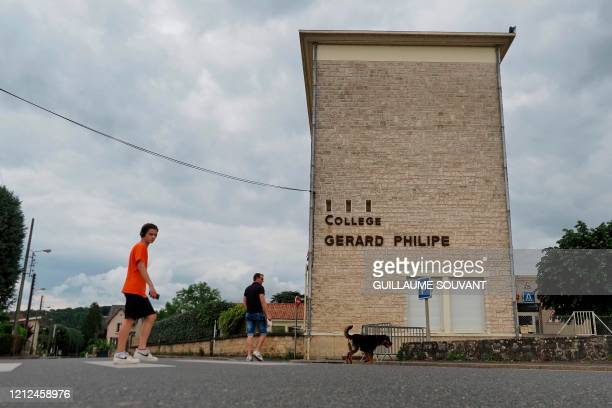 People walk on May 10 outside the Gerard Philipe secondary school in Chauvigny, central France, where a cluster of COVID-19 cases has been identified...