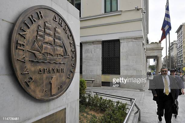 People walk on May 262011 by a monument in the center of Athens representing the last edition of the Greek drachma before the country adopted the...