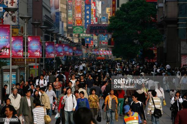 People walk on Nanjing road, China's premier shopping street October 26, 2007 in Shanghai, China. Chinese President Hu Jintao during the 17th...