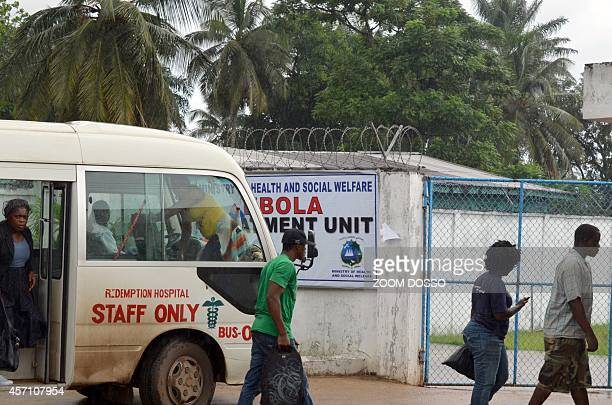 People walk on October 11 2014 outside the recently opened Ebola Island Clinic in Monrovia Health workers started a strike on October 6 to obtain a...