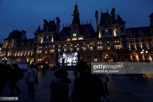 TOPSHOT People walk on Paris' city hall square on September 26 2019 where a giant screen displays pictures of late former French President Jacques...
