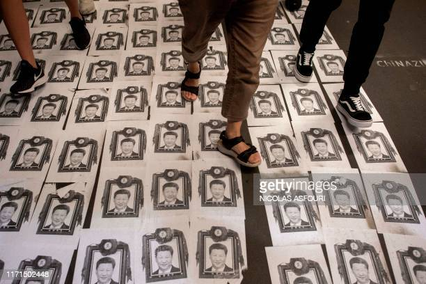 People walk on pictures of China's President Xi Jinping layed on the floor next to a rally at Edinburgh Place in Hong Kong on September 27 where...