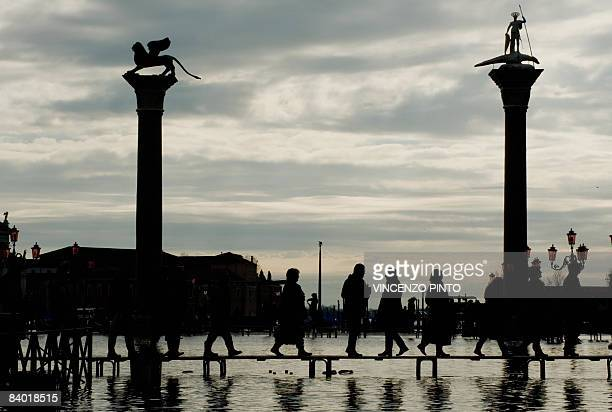 People walk on platforms to cross Piazza San Marco during floods on December 13 2008 in Venice The acqua alta stood at 109 centimeters in the morning...