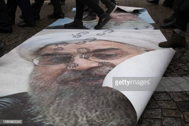 People walk on portraits of Iranian President Hassan Rouhani and Iran's Supreme Leader Ayatollah Ali Khamenei during a demonstration of the exiled...