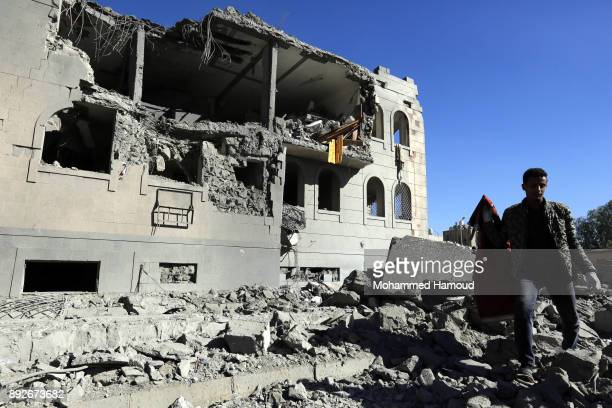 People walk on rubble of a prison after it was hit by airstrikes on December 13 2017 in Sana'a Yemen More than 12 prisoners killed and 80 others...