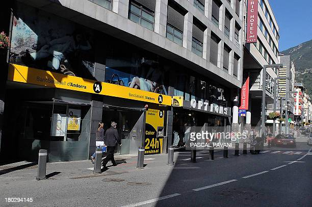 People walk on September 10 2013 past a branch of the BancSabadell d'Andorra bank in AndorralaVielle in the principality of Andorra AFP PHOTO PASCAL...