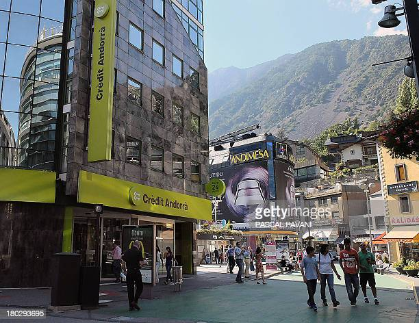 People walk on September 10 2013 past a branch of the Credit Andorra bank in the city of AndorralaVielle principality of Andorra AFP PHOTO PASCAL...