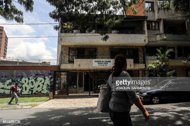 People walk on September 19 2017 past the house where druglord Pablo Escobar spent his last days and was killed as he tried to escape in Medellin...