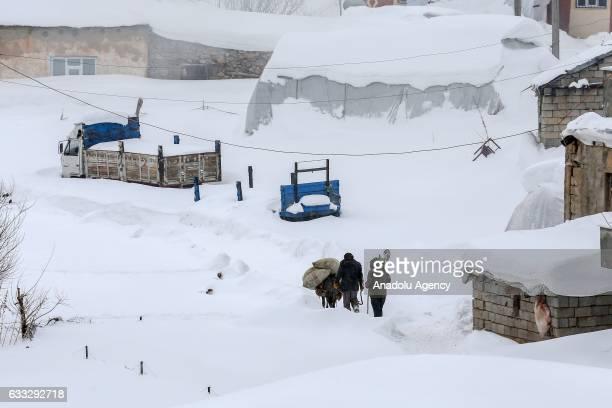 People walk on snow covered area after heavy snowfall during winter season in Yukari Narlica village of Catak district in Turkey's eastern Van...