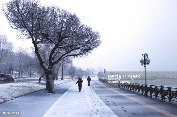 People walk on snow covered road after a heavy snowfall in Tekirdag, Turkey on December 19, 2018.