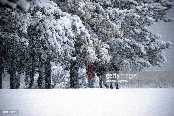 People walk on snow on October 4 2013 in Abant Nature Park Turkey The recent cold front sweeping across Turkey as a result of the low pressure system...
