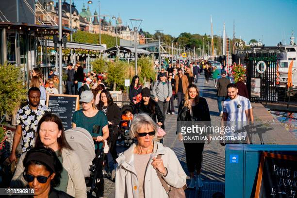 People walk on Stranvagen in Stockholm on September 19 during the novel coronavirus COVID-19 pandemic.