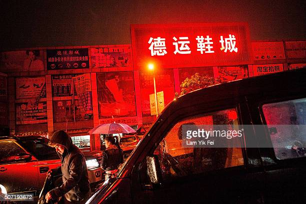 People walk on street outside of a shoe shopping mall at Houjie town on January 26 2016 in Dongguan China China's slowing economy and falling stock...