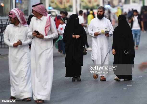 People walk on Tahlia street in the Saudi capital Riyadh on September 24 during celebrations for the anniversary of the founding of the kingdom / AFP...
