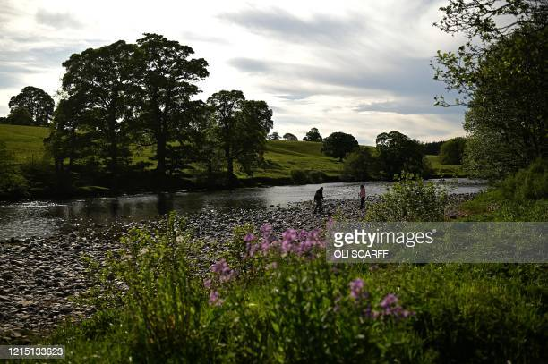 People walk on the bank of the River Tees at Barnard Castle less than 30 miles southwest of Durham north east England on May 25 a popular tourist...