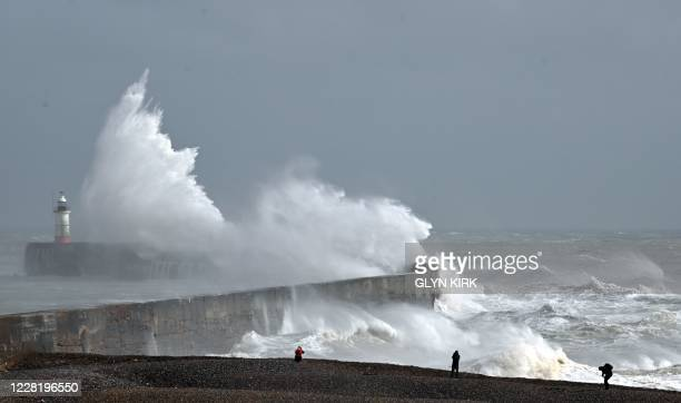 People walk on the beach as large waves crash over the harbour wall and Newhaven Lighthouse on the south coast of England on August 25, 2020. - Wind...
