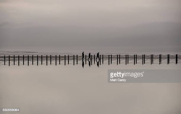 People walk on the beach as rain clouds gather above the sea front on May 11 2016 in WestonSuperMare England After the hottest day of the year the...