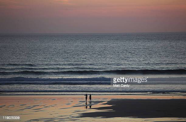People walk on the beach as the sun begins to set over the sea at Fistral Beach on July 13 2011 in Newquay England With many state schools about to...
