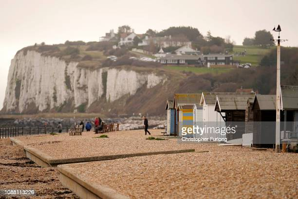 People walk on the beach at Kingsdown, near Deal, where six migrants landed by dinghy early this morning on December 30, 2018 in Dover, England. The...