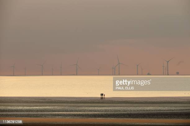 TOPSHOT People walk on the beach at New Brighton north west England at sunset on April 11 with the Burbo Bank wind farm on the Irish Sea in the...