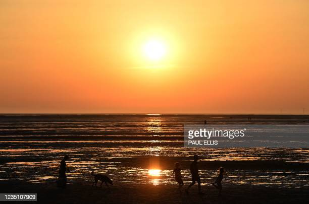 People walk on the beach at West Kirby on the north-west coast of England on September 7 as the sun sets.