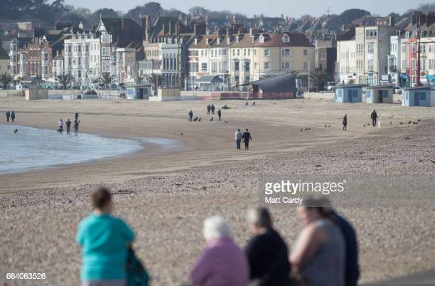 People walk on the beach at Weymouth as the resort prepares for the start of the holiday season on April 3 2017 in Dorset England With the Pound...