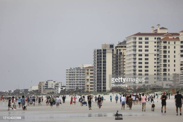 People walk on the beach in Jacksonville Beach Florida US on Saturday April 18 2020 Florida reported a total of 25269 confirmed coronavirus cases on...