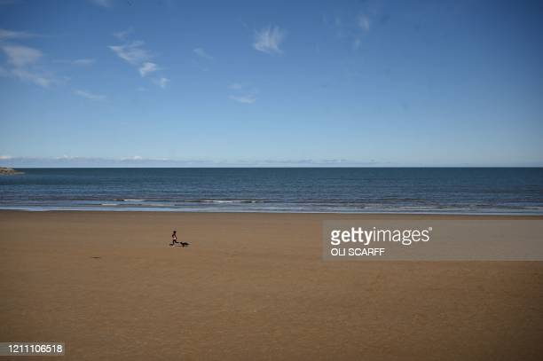 People walk on the beach in Scarborough, northeast England on April 27, 2020 as life continues in Britain under lockdown to help stem the...