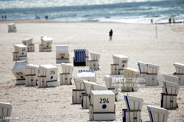 People walk on the beach of Kampen on the German North Sea island of Sylt nothern Germany on July 30 2012 Meteorologists forecast unsettled weather...