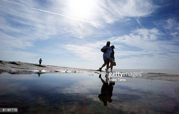 People walk on the beach on Sanibel Island August 18 2004 in Sanibel Florida Tourist destinations Captiva Island and neighboring Sanibel Island were...