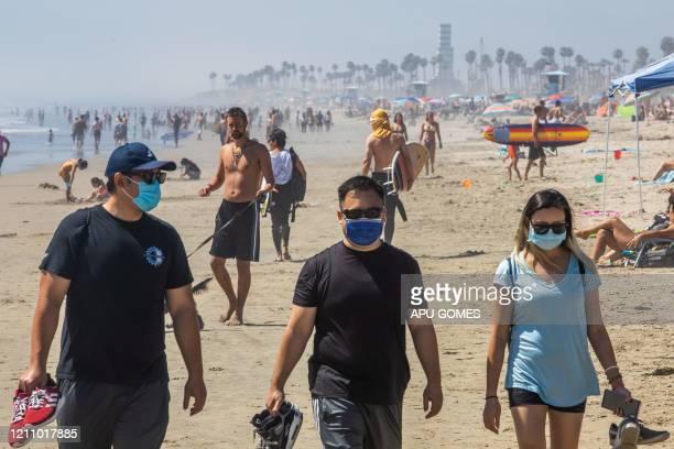 People walk on the beach some wearing masks amid the novel coronavirus pandemic in Huntington Beach California on April 25 2020 Orange County is the...