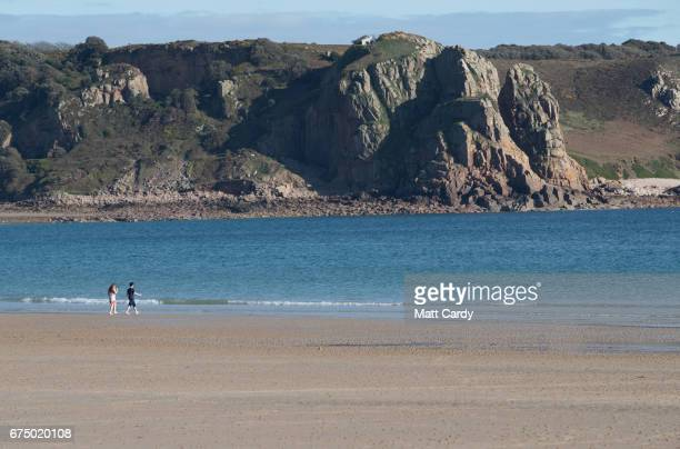 People walk on the beach St Brelade's Bay on April 13 2017 near St Helier Jersey Jersey which is not a member of the European Union is one of the top...