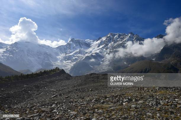 People walk on the Belvedere Glacier on September 26 2015 on the Monte Rosa The Belvedere Glacier is a valley glacier mostly covered by rocks located...