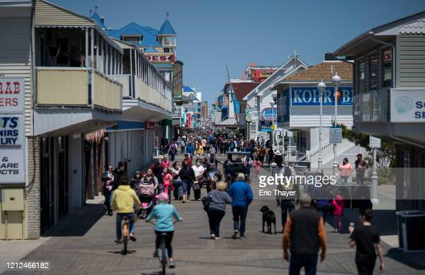 People walk on the boardwalk as the area re-opens from the coronavirus pandemic on May 10, 2020 in Ocean City, Maryland. A popular summer tourist...