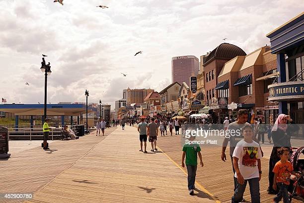 People walk on the boardwalk in Atlantic City on July 29 2014 in Atlantic City New Jersey Since January of 2014 four of Atlantic City's 11 casinos...