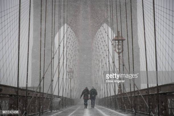 People walk on the Brooklyn Bridge during a winter storm January 4 2018 in New York City As a major winter storm moves up the Northeast corridor New...