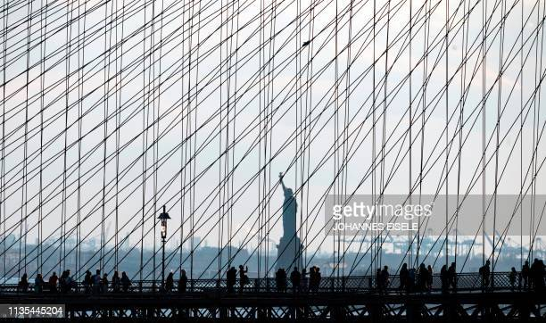 TOPSHOT People walk on the Brooklyn Bridge in front of the Statue of Liberty on April 6 2019 in New York City