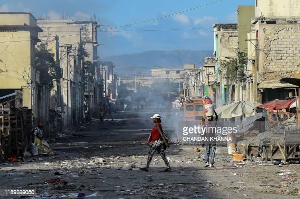 People walk on the deserted road ahead of gang shootings in downtown in Port-au-Prince, on December 20, 2019.