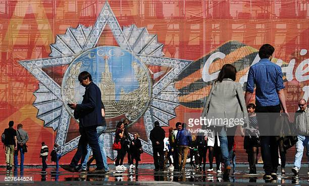 People walk on the Dvortsovaya Square with a huge poster in the background dedicated to Victory Day in St Petersburg Russia on May 2016 On 09 May...