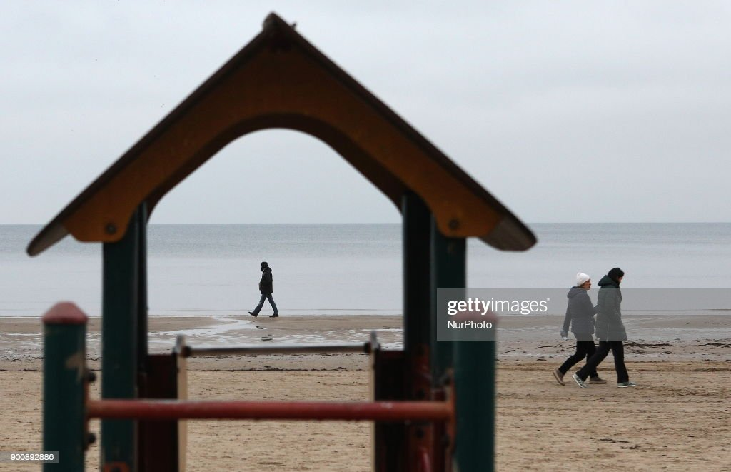 People walk on the embankment of the Gulf of Riga in Jurmala, 25 km from Riga. Latvia, Wednesday, January 3, 2018 The resort is famous for wooden Art Nouveau villas, Soviet-era sanatoriums and a long sandy beach.