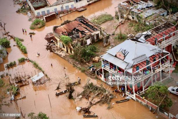 People walk on the flooded street of Buzi, central Mozambique, on March 20, 2019 after the passage of the cyclone Idai. - International aid agencies...