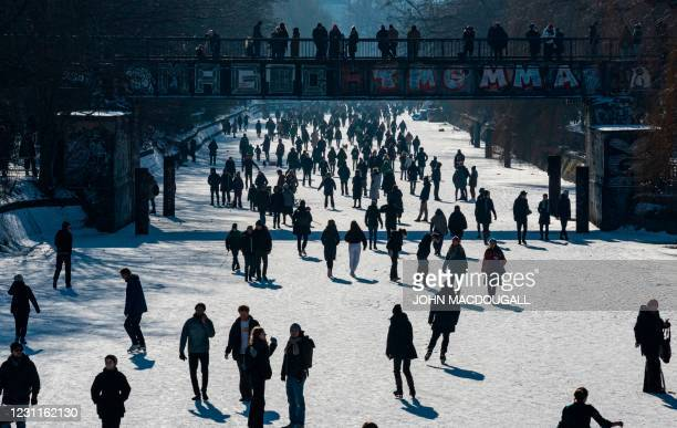 People walk on the frozen Landwehr Canal between Berlin's Treptow and Kreuzberg districts on February 14, 2021.