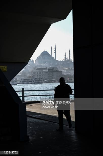 People walk on the Galata bridge in front of the Suleymaniye mosque on February 19 2019 at Karakoy district on a sunny day in Istanbul