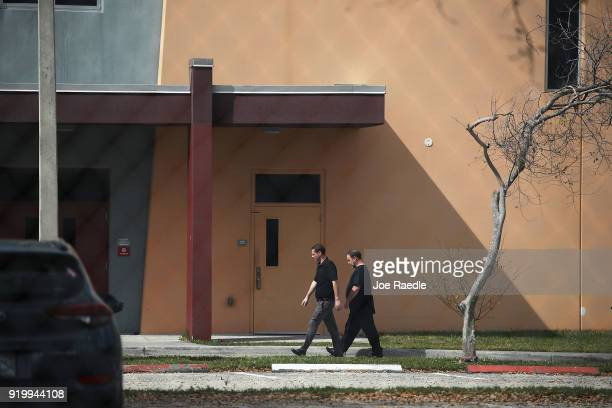 People walk on the grounds of Marjory Stoneman Douglas High School on February 18 2018 in Parkland Florida Police arrested 19 year old former student...