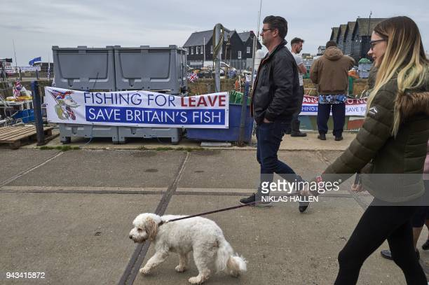 People walk on the harbourside in Whitstable southeast England on April 8 2018 during a demonstration against the Brexit transition deal that would...